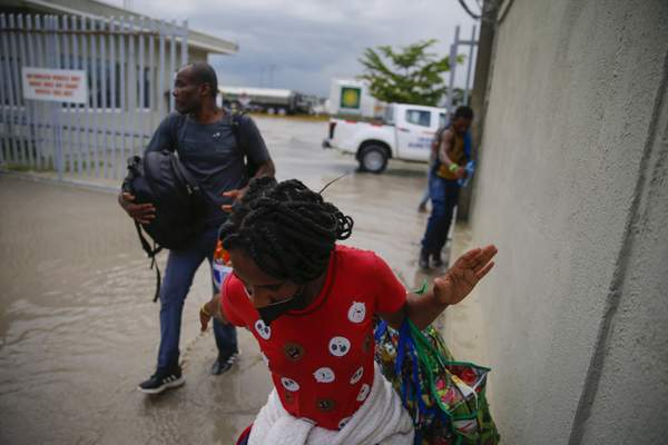 Haitians deported from the United States leave Toussaint Louverture International Airport under a rain shower in Port au Prince, Haiti, Sunday, Sep. 19, 2021. (AP Photo/Joseph Odelyn)