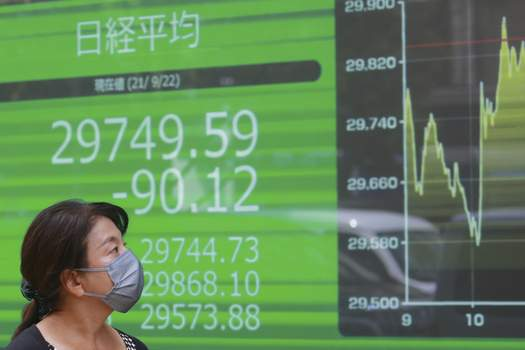 Japan Financial Markets A woman walks by an electronic stock board of a securities firm in Tokyo, Wednesday, Sept. 22, 2021. Asian shares were mostly lower on Wednesday after major indexes ended mixed on Wall Street. (AP Photo/Koji Sasahara) (Koji Sasahara STF)
