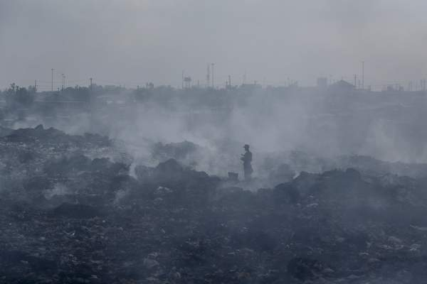 FILE - In this Tuesday, Sept. 7, 2021 file photo, a man who scavenges recyclable materials for a living walks across a mountain of garage amidst smoke from burning trash at Dandora, the largest garbage dump in the capital Nairobi, Kenya. (AP Photo/Brian Inganga, File)