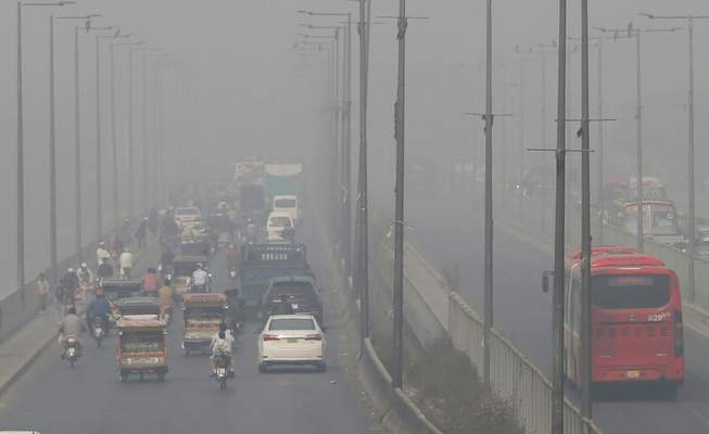 FILE - In this Wednesday, Nov. 11, 2020 file photo, vehicles drive on a highway as smog envelops the area of Lahore, Pakistan. (AP Photo/K.M. Chaudary, File)