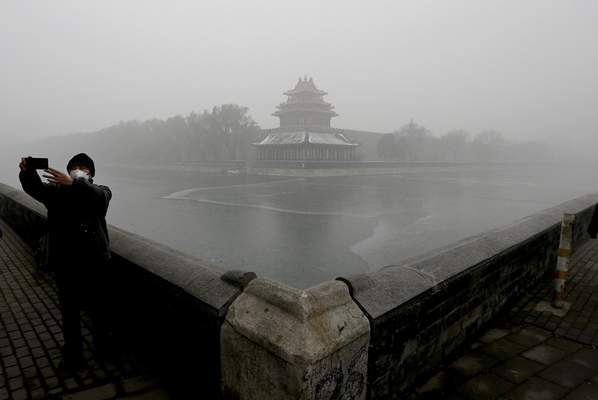 FILE - In this Tuesday, Dec. 1, 2015 file photo, a man wearing a mask to protect himself from pollutants takes a selfie near the Turret of the Forbidden City on a heavily polluted day in Beijing. (AP Photo/Andy Wong, File)