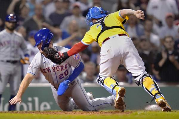 New York Mets' Pete Alonso, left, is tagged out by Boston Red Sox catcher Christian Vazquez while trying to score on a single by Michael Conforto during the fourth inning of a baseball game at Fenway Park, Tuesday, Sept. 21, 2021, in Boston. (AP Photo/Charles Krupa)
