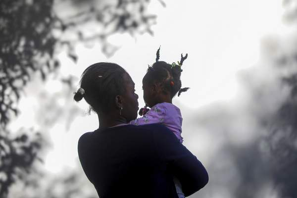 A woman holds a girl at a migrant camp in Ciudad Acuña, Mexico, Thursday, Sept. 23, 2021. Mexico security forces deployed to block immigrants, most of them from Haiti, who had camped in the park beside the Rio Grande so they can't cross the U.S.-Mexico border. (AP Photo/Felix Marquez)