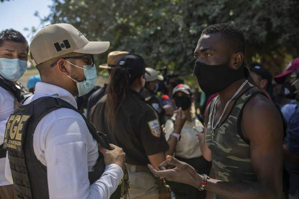 A Haitian migrant pleads with a Mexican police officer blocking access to the Rio Grande river so that immigrants can't use it to cross the U.S.-Mexico border from Ciudad Acuña, Mexico, Thursday, Sept. 23, 2021. (AP Photo/Felix Marquez)