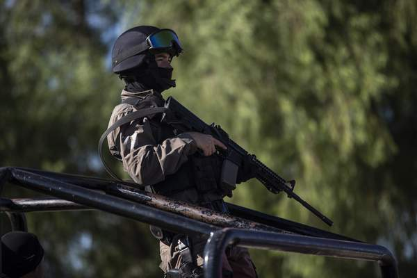 A Mexican police officer stands on the back of a vehicle blocking access to the Rio Grande so immigrants can't use it to cross the U.S.-Mexico border from Ciudad Acuña, Mexico, Thursday, Sept. 23, 2021. (AP Photo/Felix Marquez)