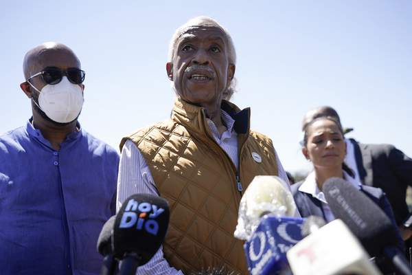 Rev. Al Sharpton, center, speaks to reporters after touring an encampment of migrants, mostly from Haiti, along the Del Rio International Bridge, Thursday, Sept. 23, 2021, in Del Rio, Texas. (AP Photo/Julio Cortez)