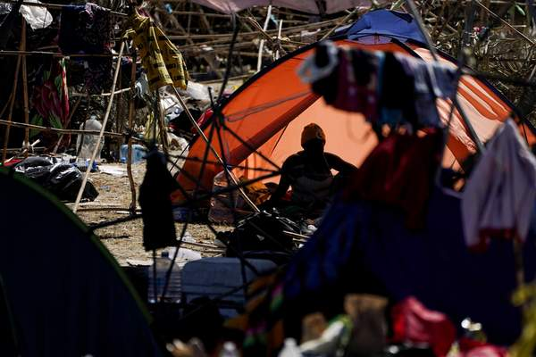 A migrant woman is seen in a tent at an encampment under the Del Rio International Bridge where migrants, many from Haiti, have been staying after crossing the Rio Grande, Thursday, Sept. 23, 2021, in Del Rio, Texas. (AP Photo/Julio Cortez)
