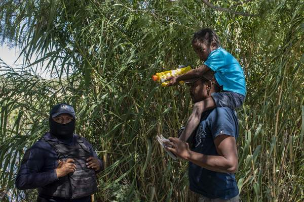 A Haitian migrant talks to with a Mexican police officer blocking access to the Rio Grande river so that immigrants can't use it to cross the U.S.-Mexico border from Ciudad Acuna, Mexico, Thursday, Sept. 23, 2021. (AP Photo/Felix Marquez)
