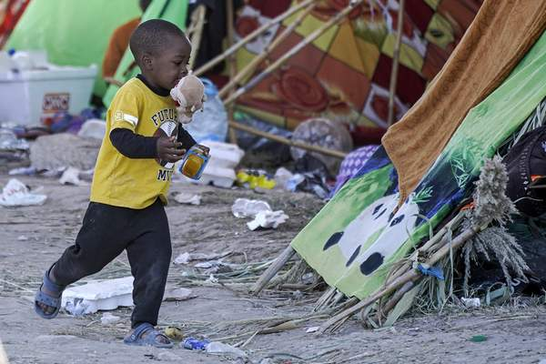 A migrant child runs with a food he received from volunteers at an encampment under the Del Rio International Bridge where migrants, many from Haiti, have been staying after crossing the Rio Grande, Thursday, Sept. 23, 2021, in Del Rio, Texas. (AP Photo/Julio Cortez)