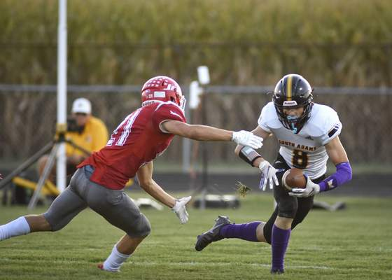 Mike Moore | The Journal Gazette South Adams wide receiver Trey Schoch looks to break a tackle Friday in the first quarter against Adams Central in Monroe.
