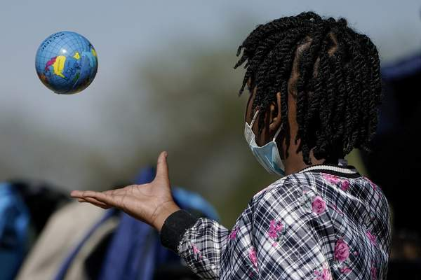 Associated Press A Haitian girl plays with a ball Friday in Del Rio, Texas, while waiting to board a bus to Houston provided by a humanitarian group after she and her family were released from U.S. custody.