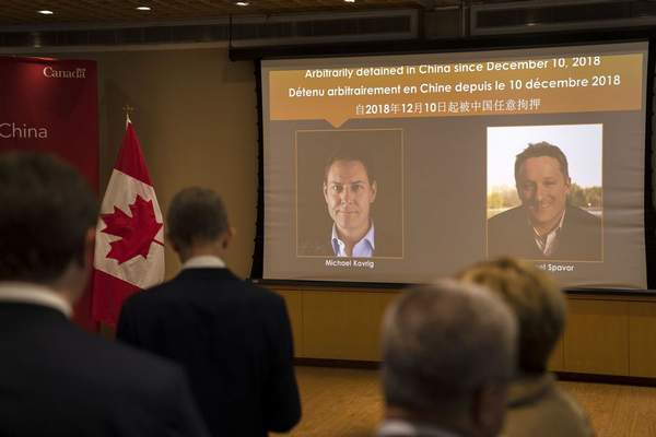 A video screen displays images of Canadians Michael Kovrig, left, and Michael Spavor. (AP Photo/Mark Schiefelbein)