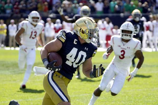 Notre Dame linebacker Drew White heads for the end zone for his second interception for a touchdown against Wisconsin during the second half of an NCAA college football game Saturday, Sept. 25, 2021, in Chicago. Notre Dame won 41-13. (AP Photo/Charles Rex Arbogast)