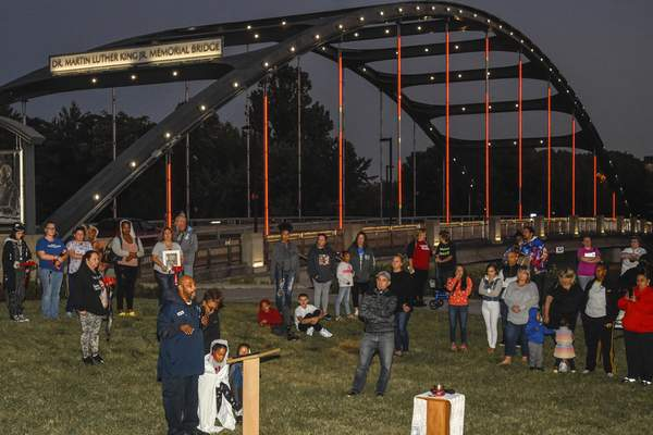 Mike Moore | The Journal Gazette Families of victims hold a remembrance ceremony Saturday near the Martin Luther King Jr. Memorial Bridge downtown.