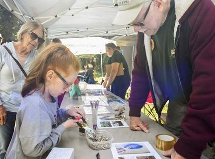 Michelle Davies   The Journal Gazette Lauren Conkle-Wesolowski, 8, of Indianapolis picks up sunflower seeds as Russ Voorhees explains how birds use their beaks to eat during Saturday's event.