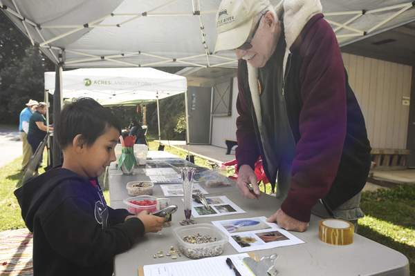 Michelle Davies | The Journal Gazette Hayden Daniels, 5, listens as Russ Voorhees, with Little River Wetlands Project, explains the different ways birds use their beaks to eat during Saturday's Feather Fest at Lindenwood Nature Preserve.