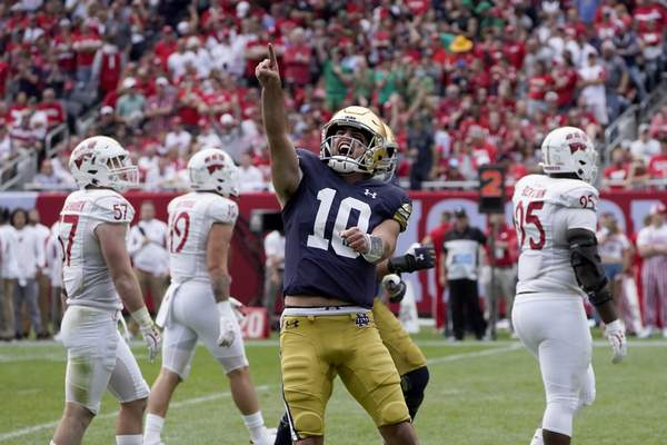 Associated Press Notre Dame quarterback Drew Pyne celebrates his touchdown pass to wide receiver Kevin Austin Jr. during the second half against Wisconsin on Saturday in Chicago.