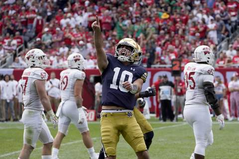Notre Dame Wisconsin Football Associated Press Notre Dame quarterback Drew Pyne celebrates his touchdown pass to wide receiver Kevin Austin Jr. during the second half against Wisconsin on Saturday in Chicago.  (Charles Rex ArbogastSTF)
