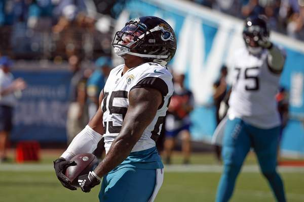 Jacksonville Jaguars running back James Robinson, left, celebrates his 4-yard touchdown run against the Arizona Cardinals during the second half of an NFL football game, Sunday, Sept. 26, 2021, in Jacksonville, Fla. (AP Photo/Stephen B. Morton)