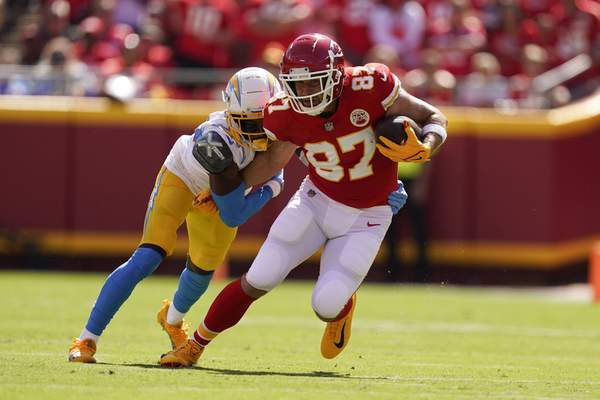 Kansas City Chiefs' Travis Kelce (87) runs out of a tackle by Los Angeles Chargers' Michael Davis (43)[ during the first half of an NFL football game, Sunday, Sept. 26, 2021, in Kansas City, Mo. (AP Photo/Charlie Riedel)