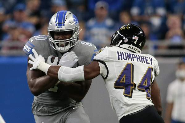 Detroit Lions tight end Darren Fells (80) tries to avoid Baltimore Ravens cornerback Marlon Humphrey (44) in the first half of an NFL football game in Detroit, Sunday, Sept. 26, 2021. (AP Photo/Tony Ding)