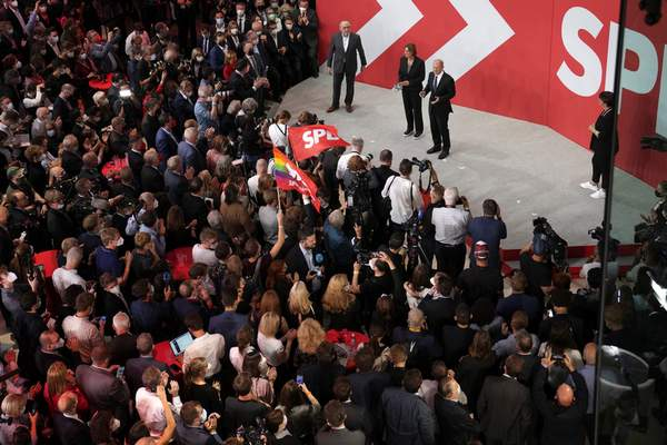 Olaf Scholz, Finance Minister and SPD candidate for Chancellor, center, addresses his supporters after German parliament election at the Social Democratic Party, SPD, headquarters in Berlin, Sunday, Sept. 26, 2021. (AP Photo/Michael Sohn)