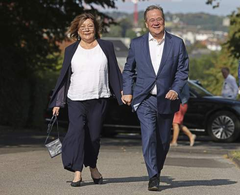 Armin Laschet, right, Christian Democratic Union parties candidate foe Chancellery and Minister President of North Rhine-Westphalia and his wife Susanne arrive to vote for the German parliament election in Aachen, Germany, Sunday, Sept. 26, 2021. (Rolf Vennenbernd/dpa via AP)