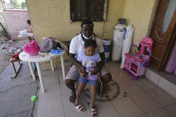 Mensah Montant and his daughter Rachel sit on their porch in Ciudad Acuna, Friday, Sept. 24, 2021. (AP Photo/Fernando Llano)