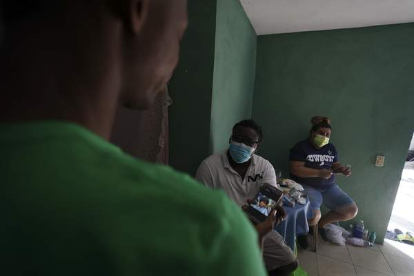 Mensah Montant, center, and his wife Virginia Salazar visit with a Haitian migrant at an apartment in Ciudad Acuna, Friday, Sept. 24, 2021. (AP Photo/Fernando Llano)