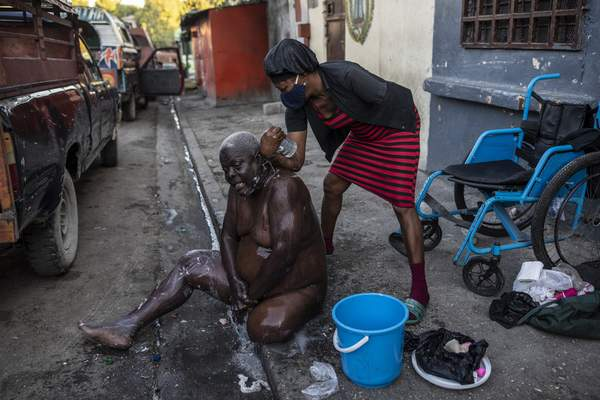Marie Joseph bathes her friend Jean Robert outside a shelter for the internally displaced where they live due to police violence in Port-au-Prince, Haiti, Thursday, Sept. 16, 2021. (AP Photo/Rodrigo Abd)