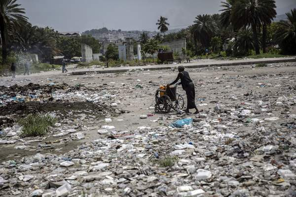 A woman pushes a wheelchair, carrying her empty water containers, through an empty street littered with trash near the judiciary and legislative buildings, in Port-au-Prince, Haiti, Tuesday, Sept. 22, 2021. (AP Photo/Rodrigo Abd)