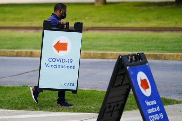 FILE - In this Sept. 14, 2021, file photo, a worker posts placard for a COVID-19 vaccination clinic at the Reading Area Community College in Reading, Pa. (AP Photo/Matt Rourke, File)