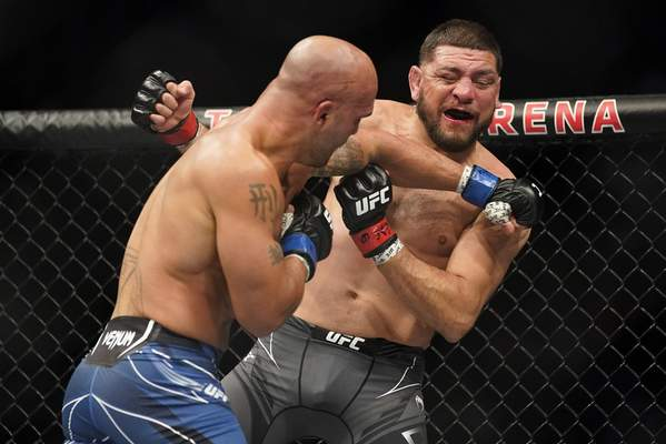Robbie Lawler, left, throws a punch against Nick Diaz during a middleweight mixed martial arts bout at UFC 266, Saturday, Sept. 25, 2021, in Las Vegas. (AP Photo/John Locher)
