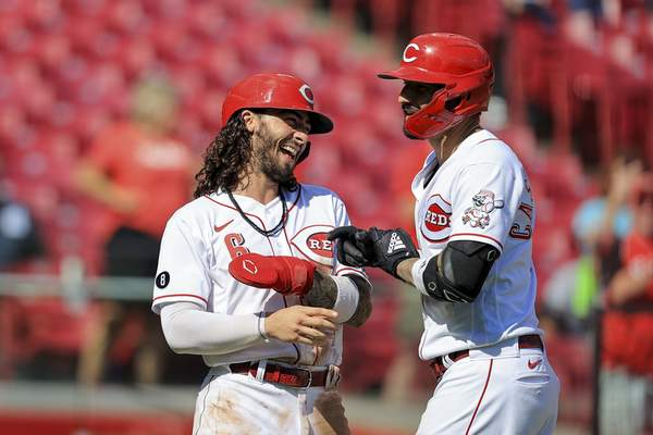 Cincinnati Reds' Nick Castellanos, right, celebrates hitting a three-run home run with Jonathan India during the sixth inning of a baseball game against the Pittsburgh Pirates in Cincinnati, Monday, Sept. 27, 2021. (AP Photo/Aaron Doster)