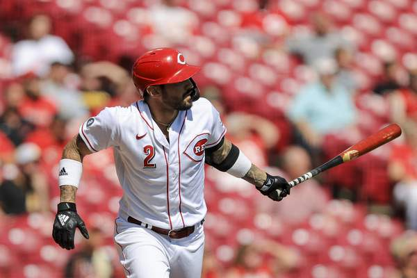 Cincinnati Reds' Nick Castellanos watches as he hits a sacrifice fly during the first inning of a baseball game against the Pittsburgh Pirates in Cincinnati, Monday, Sept. 27, 2021. (AP Photo/Aaron Doster)