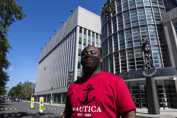 """An unidentified supporter of R&B singer R. Kelly, wears a mask reading Free R. Kelly outside Brooklyn Federal Court House on Monday, Sept. 27, 2021, in New York. The 54-year-old Kelly, perhaps best known for the 1996 smash hit """"I Believe I Can Fly, """" has pleaded not guilty to racketeering charges accusing him of sexually abusing women, girls and boys for more than two decades. (AP Photo/Brittainy Newman)."""