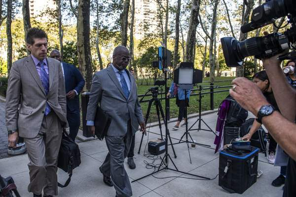 """CORRECTS SPELLING OF DEVERAUX - Attorney Deveraux Cannick, representing R&B star R. Kelly, center, arrives at Brooklyn Federal Court House on Monday, Sept. 27, 2021, in New York. The jury resumed deliberations on Monday at the sex trafficking trial of Kelly. The 54-year-old singer of the smash hit """"I Believe I Can Fly"""" has denied any wrongdoing. (AP Photo/Brittainy Newman)"""