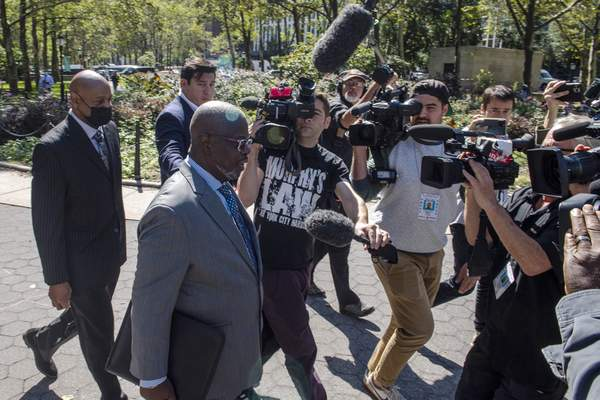 """Deveraux Cannick, attorney for R. Kelly, is surrounded by the media during a break at the Brooklyn Federal Court House on Monday, Sept. 27, 2021, in New York. The 54-year-old Kelly, perhaps best known for the 1996 smash hit """"I Believe I Can Fly, """" has pleaded not guilty to racketeering charges accusing him of sexually abusing women, girls and boys for more than two decades. (AP Photo/Brittainy Newman)"""
