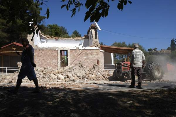 Residents pass next to a damaged Greek Orthodox chapel after a strong earthquake in Arcalochori village on the southern island of Crete, Greece, Monday, Sept. 27, 2021. A strong earthquake with a preliminary magnitude of 5.8 has struck the southern Greek island of Crete, and Greek authorities say one person has been killed and several more have been injured. (AP Photo/Harry Nikos)