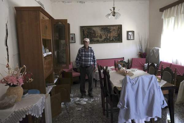 An elderly man stands inside his house after a strong earthquake in Roussochoria village on the southern island of Crete, Greece, Monday, Sept. 27, 2021. A strong earthquake has struck the Greek island of Crete. One person has been killed and at least nine others have been injured. Homes and churches were damaged and rock slides occurred near the country's fourth-largest city.(AP Photo/Harry Nakos)