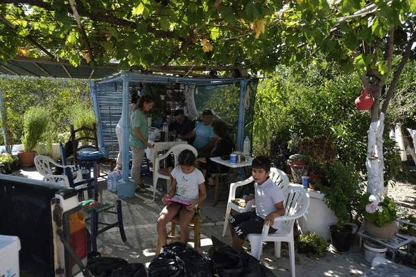 Residents sit at a yard after an earthquake in Sampas village on the southern island of Crete, Greece, Monday, Sept. 27, 2021. A strong earthquake has struck the Greek island of Crete. One person has been killed and at least nine others have been injured. Homes and churches were damaged and rock slides occurred near the country's fourth-largest city. (AP Photo/Harry Nakos)