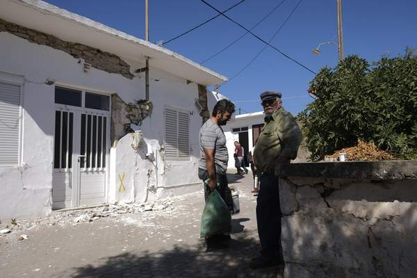 Residents stand outside a damaged house after an earthquake in Sampas village on the southern island of Crete, Greece, Monday, Sept. 27, 2021. A strong earthquake has struck the Greek island of Crete. One person has been killed and at least nine others have been injured. Homes and churches were damaged and rock slides occurred near the country's fourth-largest city. (AP Photo/Harry Nakos)