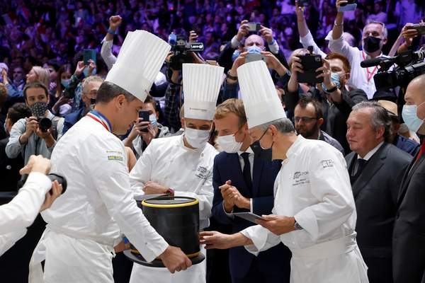 French President Emmanuel Macron, second right, looks at a lunchbox at the Bocuse d'Or gastronomy contest during the International Catering, Hotel and Food Trade Fair (SIRHA) in Lyon, central France, Monday Sept. 27, 2021. (Ludovic Marin, Pool Photo via AP)