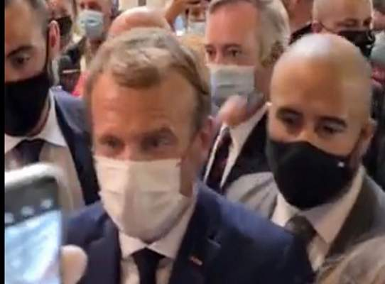 This image from video made available by Lyonmag.com shows an egg thrown toward French President Emmanuel Macron, left, to hit him on the shoulder as he walks through the restaurant trade fair in Lyon, France, Monday Sept. 27, 2021. (LYONMAG.COM via AP)