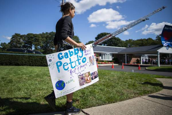 A woman carries a placard in honor of Petito as people attend the funeral home viewing of Gabby Petito at Moloney's Funeral Home in Holbrook, N.Y. Sunday, Sept. 26, 2021. (AP Photo/Eduardo Munoz Alvarez)