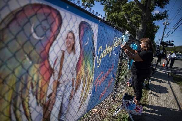 A woman places a decoration near a poster after attending the funeral home viewing of Gabby Petito at Moloney's Funeral Home in Holbrook, N.Y. Sunday, Sept. 26, 2021. (AP Photo/Eduardo Munoz Alvarez)