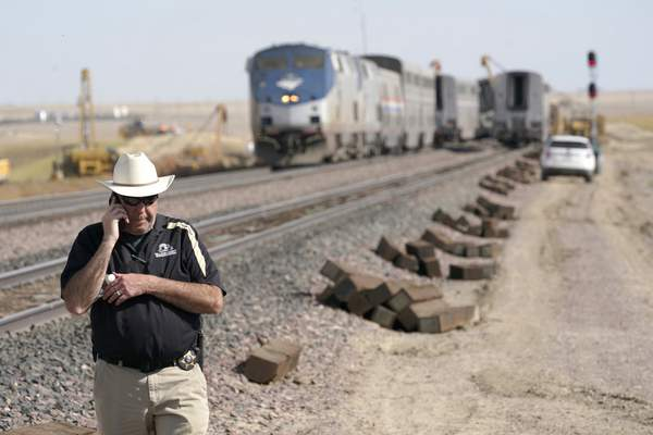 Jason Jarrett, of the Gallatin County (Mont.) Sheriff's Office, talks on a phone Sunday, Sept. 26, 2021, near an Amtrak train that derailed a day earlier just west of Joplin, Mont., killing three people and injuring others. (AP Photo/Ted S. Warren)