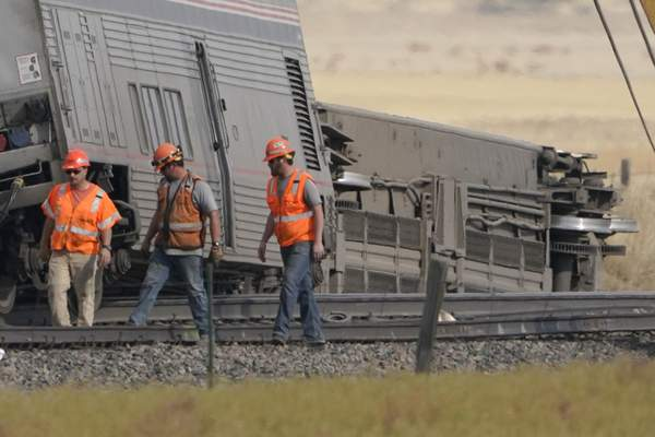 Workers walk Sunday, Sept. 26, 2021, next to cars from an Amtrak train that derailed Saturday just west of Joplin, Mont. (AP Photo/Ted S. Warren)