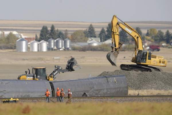 Workers walk near derailed cars from an Amtrak train, Sunday, Sept. 26, 2021, that derailed the day before just west of Joplin, Mont., killing three people and injuring others. (AP Photo/Ted S. Warren)