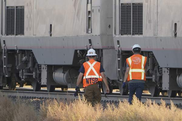 A person wearing a National Transportation Safety Board vest and hardhat, left, walks with another person, Sunday, Sept. 26, 2021, near engines from an Amtrak train that derailed Saturday, just west of Joplin, Mont. (AP Photo/Ted S. Warren)